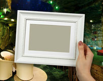 Wooden frame in woman hands on the background interior elegant restaurant royalty free stock photo