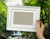 Wooden frame in woman hands on the background natural spring waterfall stock photos