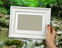 Wooden frame in woman hands. background of the Natural Spring Waterfall Stock Images