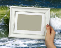 Wooden frame in woman hands on the background sea waves on beaches. Wooden frame in beautiful woman hands on the background sea waves on beaches, sands, foam royalty free stock image