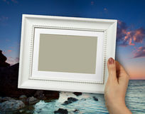 Wooden frame in woman hands on the background sunset Royalty Free Stock Image