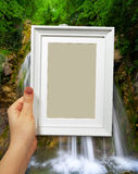 Wooden frame in woman hands on the background waterfall in forest Royalty Free Stock Images