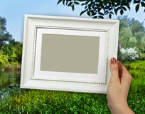 Wooden frame in woman hands on the countryside scene background Stock Photography