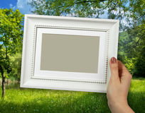 Wooden frame in woman hands on the countryside scene background royalty free stock images