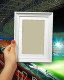 Wooden frame in woman hands. football stadium on the background Stock Photography