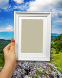 Wooden frame in woman hands on the Mountain background royalty free stock photo