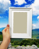 Wooden frame in woman hands on the Mountain background Royalty Free Stock Images
