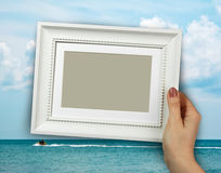 Wooden frame in woman hands on the Sea water background Stock Photos