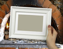 Wooden frame in woman hands. Warm Hearth on the background Royalty Free Stock Image