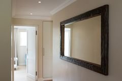 Wooden framed mirror on white wall. At home Stock Photo