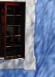 Wooden framed window in blue and white painted wall Stock Photo