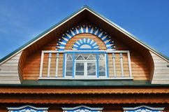 Wooden fretted roof with window on blue sky Royalty Free Stock Image