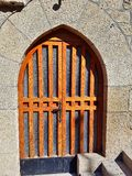 Wooden front door with arch and glass at an old stone building. Stock Photo