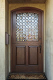 Wooden front door of home with ornate glass detail Stock Photo