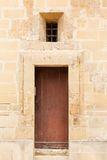 Wooden front door to the house. Old wooden front door and window to the house in the Mediterranean Stock Photos
