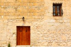 Wooden front door to the house. Old wooden front door and window to the house in the Mediterranean Stock Photo