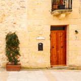 Wooden front door to the house. Old wooden front door and window to the house in the Mediterranean Stock Image