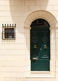 Wooden front door to the house and window. Green wooden front door to the house in the Mediterranean Royalty Free Stock Image