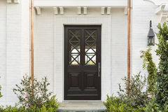 Wooden front door of white brick home with plants Royalty Free Stock Image
