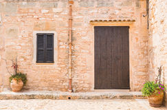 Wooden Front Door and window shutters. Front view of an mediterranean house with rustic brown wooden door, shutters, stone wall and flower pots decoration Royalty Free Stock Photography