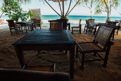 Wooden furniture in beach cafe on background sea. Cafe with a view blue ocean stock image