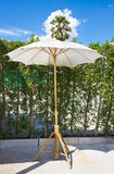 Wooden furniture covered by umbrella Royalty Free Stock Image