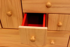 Wooden furniture. Detail of wooden furniture with red drawers at interior Royalty Free Stock Image