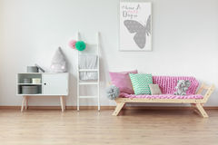 Wooden furniture in kid room. Modern wooden furniture in Scandinavian style in bright spacious kid room royalty free stock images