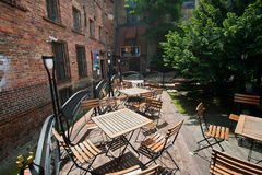Wooden furniture of outdoor cafe without people at the gothic building Stock Photos