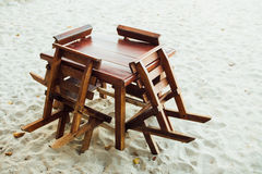 Wooden furniture on sandy beach. Table and chairs stand on sand beach Royalty Free Stock Image