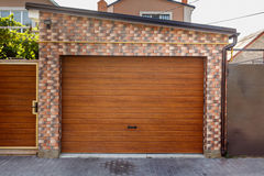 Wooden Garage Door with colored brick wall background. Dark Wooden Garage Door with colored brick wall background Royalty Free Stock Images