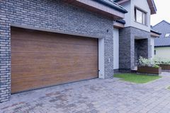 Wooden garage door of detached house. View of wooden garage door and main entrance of detached house royalty free stock photos