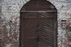 A wooden garage door in a stone wall. Vintage stock photography