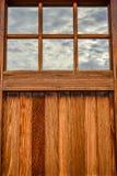 Wooden garage door with window. Wooden garage door panel with reflective windows Royalty Free Stock Photo