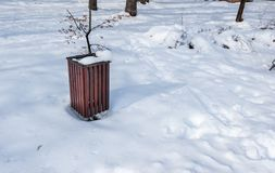 Wooden garbage or junk can for trash in the park covered with snow in the winter season to protect from environment pollution royalty free stock images