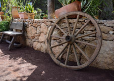 Wooden garden decors, bench and wheel. Stylish garden decors, wooden bench and wheel Royalty Free Stock Images