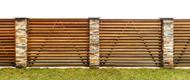 Wooden garden fence with stone paved pillars guarding private pr. Operty. Fence made of horizontal wooden planks and backyard lawn stock images