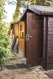 Wooden garden shed. With the door open and a neat path leading to the entrance under shady trees stock photo
