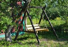 Wooden Garden Swing. Garden Swing Seat in tree shadow Royalty Free Stock Photo