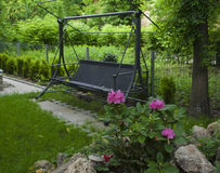 Wooden garden swing in a green garden with pink flowers Royalty Free Stock Image