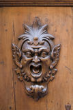 Wooden gargoyle. Carved gargoyle adorning a wooden door in Siena, Italy royalty free stock images