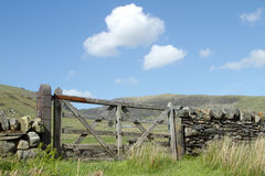 Wooden gate. A rustic wooden gate on upland farmland with a stone wall and mountains in the distance Stock Photography