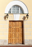 Wooden gate with arch in yellow classical facade royalty free stock photos