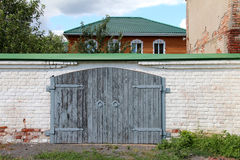 Wooden gate. And brick wall in the village Royalty Free Stock Images