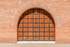 A wooden gate with a door in the brick wall. Space to insert text. Royalty Free Stock Image