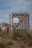 Private sign. A wooden gate and fence with a 'private' sign and warning 'trespassers will be prosecuted' on a sand dune against a blue sky with cloud Stock Images