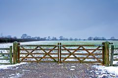 Wooden gate next to a wintery field with black sheep Stock Photos