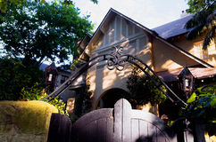 Wooden gate with ornate metal decorations in front of Townhouse stock photography