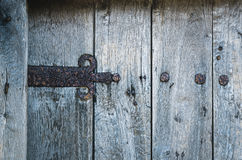 Wooden gate with rusted iron hinge. Part of old wooden gate with rusted iron hinge Royalty Free Stock Images