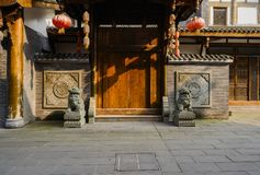 Wooden gate with stone lions of old-fashioned building in sunny Stock Photo